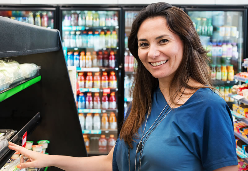 Woman shopping at convenience store open-air cooler.