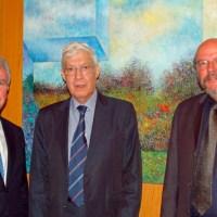 Schmückt mit seinem Gemälde die Uni: Mario Diaz Suarez (Mitte) mit Helmut Schröer (links) und Peter Schwenkmezger (rechts) - 5VIER