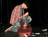 Paul Hilger repariert seine Gitarre während des Auftritts bei RLP Poetry Slam Landesmeisterschaft 2014 Eröffnungsgala. - 5VIER