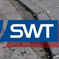 Das Bild zeigt eine defekte Strasse in Trier mit dem Logo der Stadtwerke Trier. Foto: 5vier.de