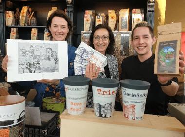 Künstlerin Anja Streese mit der aktuellen Trierer Kulturaktie, Hiltrud Zock (Kulturstiftung Trier) mit der Trier Schokolade, Falk Schramer (Mondo del Caffè) mit dem Trier Kaffee