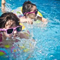 Zwei Kinder mit Sonnenbrille und Schwimmreifen im Freibad.