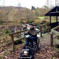 Dr. Holger Tülp testet ein Gespann aus Rollstuhl und Zuggerät auf dem zertifizierten barrierefreien Komfort-Weg rund um den Stausee Irrhausen. Bildquelle: Naturpark Südeifel/Dr. Holger Tülp.
