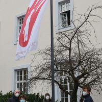 Auch in der Corona-Krise hängt die Red-Hand-Flagge vor dem Rathaus. OB Wolfram Leibe (l.) hisste sie zusammen mit Schülern vom FWG, HGT und der IGS. Bildquelle: Presseamt Trier