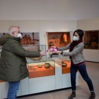 Der erste Besucher erhält den neuen Kurzführer durchs Museum von der stellvertretenden Direktorin Mechthild Neyses-Eiden. Bildquelle: GDKE-Rheinisches Landesmuseum Trier, Franz Stark