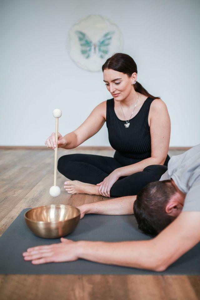 Eines der Angebote ist die Klangschalen-Meditation. Hier Selina an der Klangschale und Karsten in der Haltung des Kindes. Bildrechte: Katharina Jung