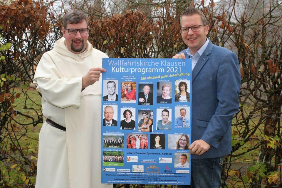 Pater Albert Seul und Tobias Marenberg präsentieren das Plakat zu Kultur in der Wallfahrtskirche 2021. Bildquelle: Tobias Marenberg