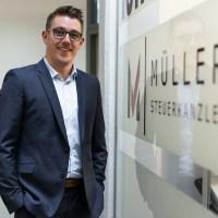 Steuerberater Daniel Müller steht am Eingang seiner Kanzlei vor dem Türschild. - Foto: Frederik Herrmann - 5vier.de