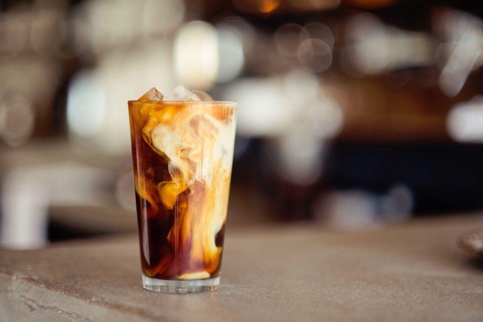 Das Foto zeigt ein Glas mit Milchkaffee stehend auf einem Holztisch. Foto: Photo by Demi DeHerrera on Unsplash