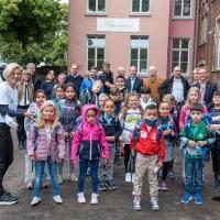 Zwei Damen des Inner Wheel Club Trier helfen den Kindern beim Aufladen der Schulranzen. Im Hintergrund freuen sich Ideengeber und Sponsoren gemeinsam mit den Mädchen und Jungen. Bildquelle: Rolf Lorig
