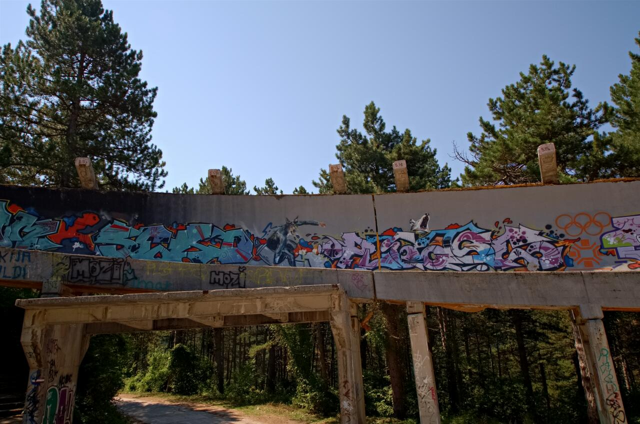 Streetart in Sarajevo: panorama of a part f the bobsleigh run, slightly different angle with another wolf on the left, this one shooting laser beams