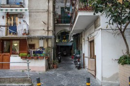 Typical residential in Naples with a little shrine for the mother Mary, a self-constructed annex and a couple of Vespas in front.