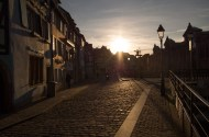 Squinting in the lowlying sun on a cobbled street in Colmar.