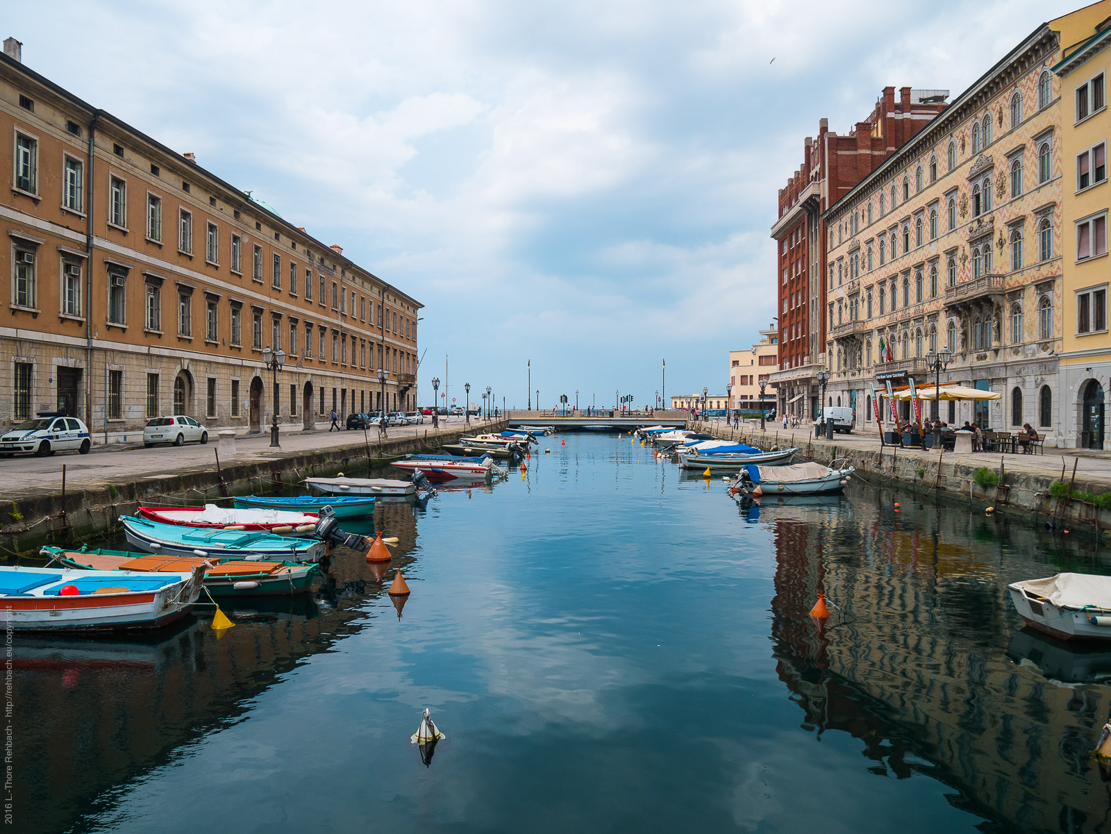 Canal Grande in Trieste with small boats and pedestrian bridge.