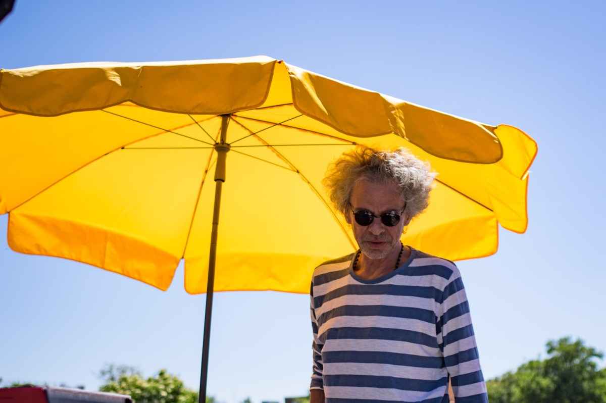 Man in a striped shirt in front of a yellow umbrella