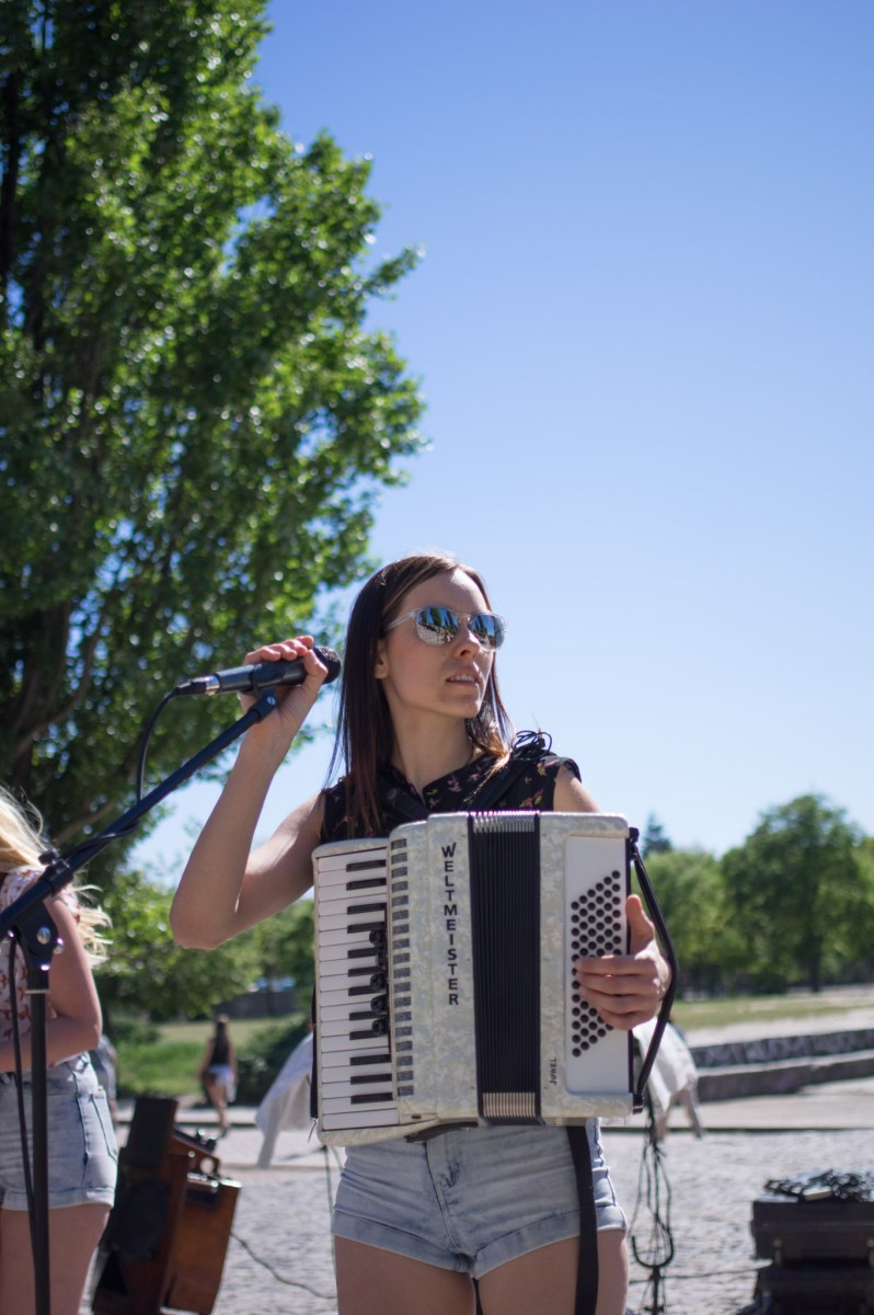 Woman playing the accordion and singing on an open-air-stage in Berlin