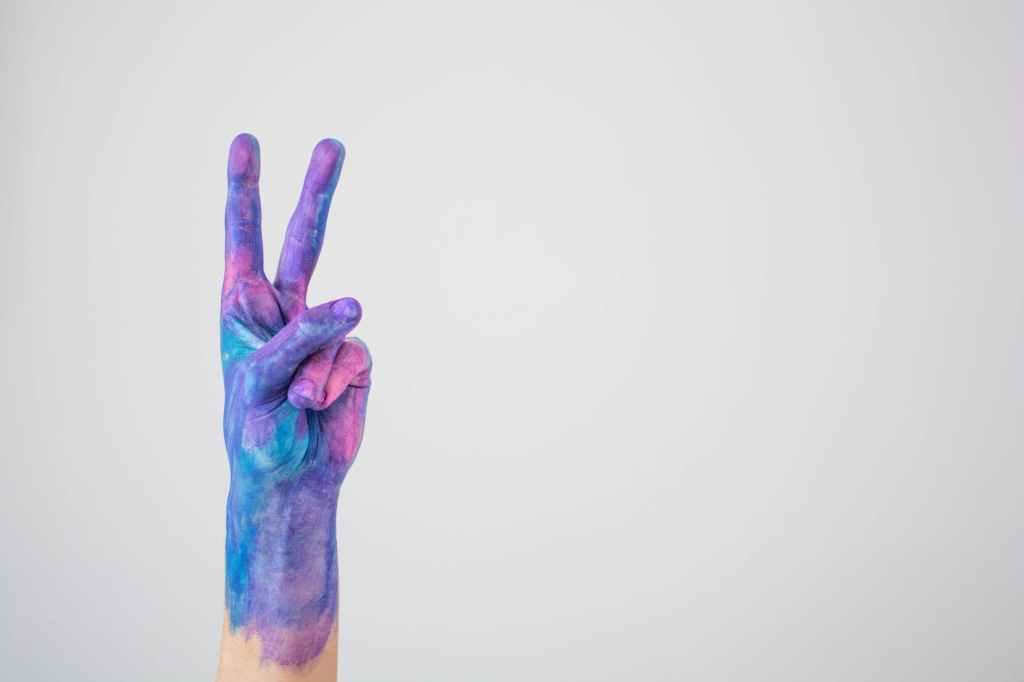 Imagem de uma mão pintada fazendo sinal de dois, como um modo de pensar positivo diante das crises. Fim da descrição.