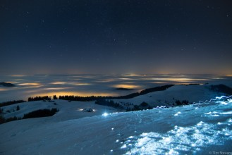 Looking north towards the Jura from the top of La Berra. Note the bobbing head torch of the ski tourer and the flashing light of a passing plane.