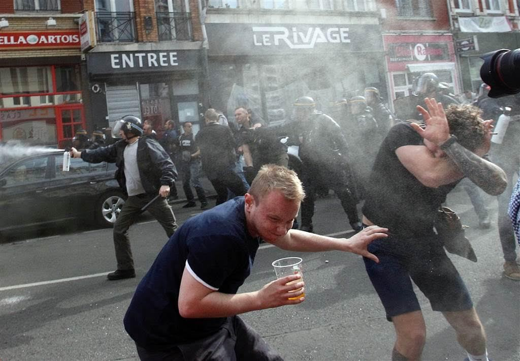 English soccer fans run for cover after getting sprayed with pepper spray by French police during scuffles in downtown Lille, northern France Michel Spingler