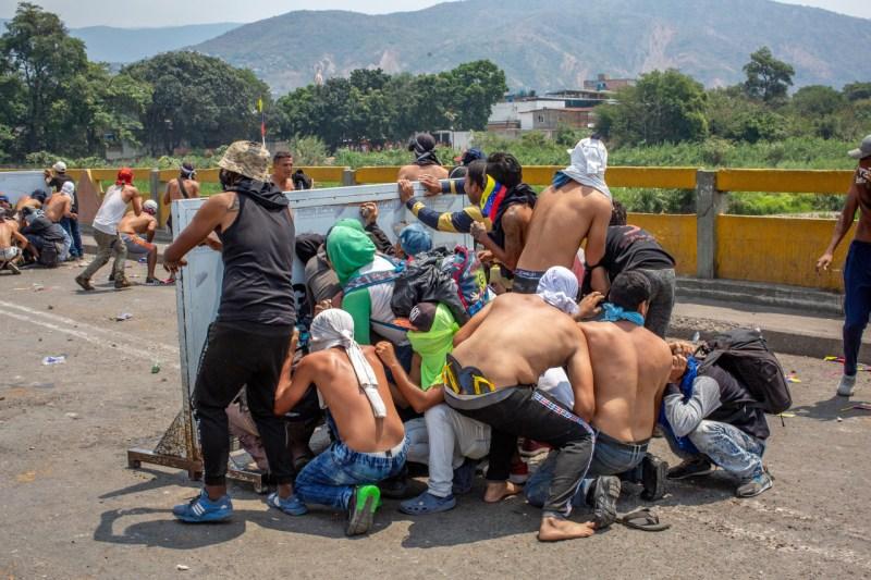 Группа демонстрантов укрывается во время столкновения с сотрудниками венесуэльской национальной полиции на Международном мосту Симона Боливара в Кукуте, Колумбия, 23 февраля. Столкновения вдоль границы застряли на караванах с гуманитарной помощью.