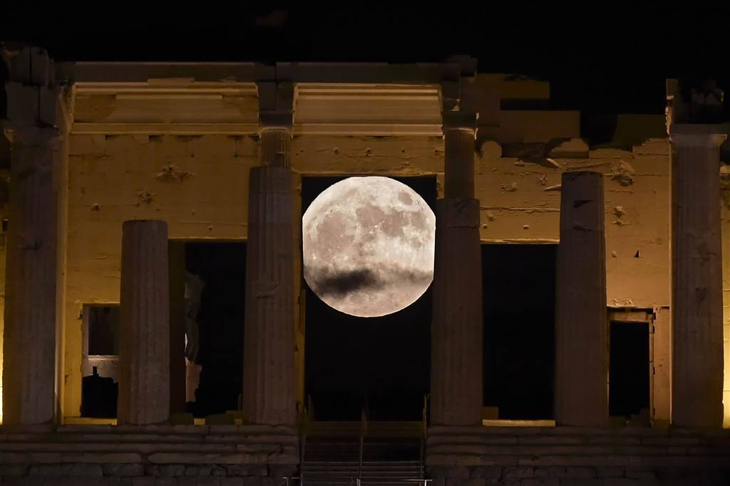 The 'supermoon' rises behind the Propylaea above the Ancient Acropolis hill in Athens. ARIS MESSINIS