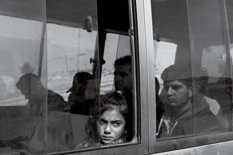 Нухат Абдул Хамид, 9 лет, из сирийского курдского города Дарбасия, на автобусе, перевозящем беженцев в лагерь Бардараш в Ираке 1 ноября.
