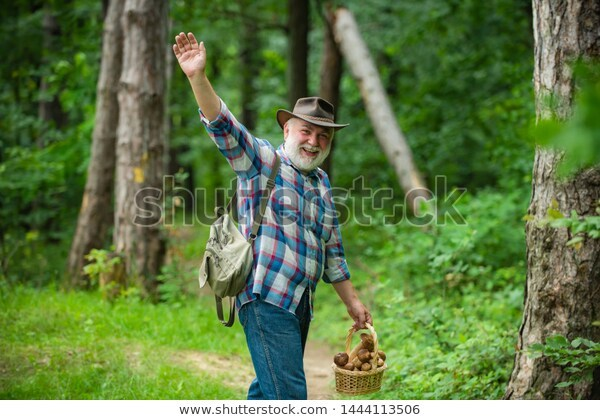 Old bearded man waving at the camera and holding a basket of mushrooms.