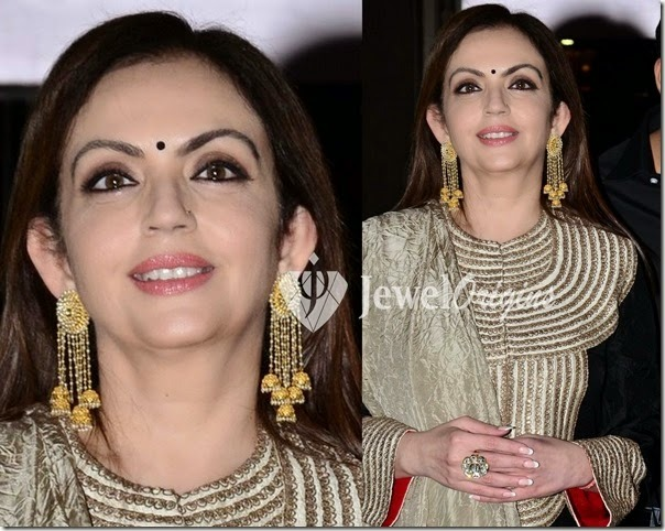 Nita Ambani wearing two of her gold medals on her ears.
