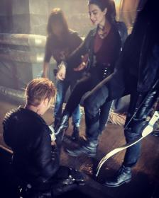 Dom kneeling, cleaning Eme's and Matt's shoes. All three are in costume.