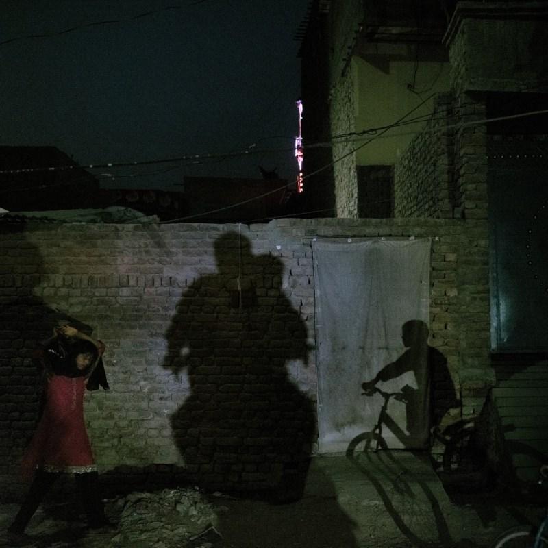 27 июня в Джейкобабаде проходят различные мероприятия: девушка возвращается домой с продуктами; мальчик едет на велосипеде; и отец с сыном едут домой на мотоцикле.