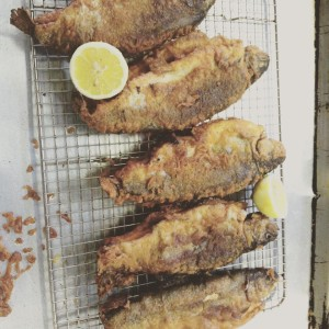 a pan of local fried trout with lemon