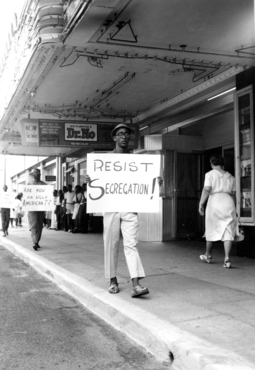 The slow pace of social change in Florida prompted many African-Americans to take action. In this image, dated 1962, young men and women protest outside the Florida Theater in Tallahassee.