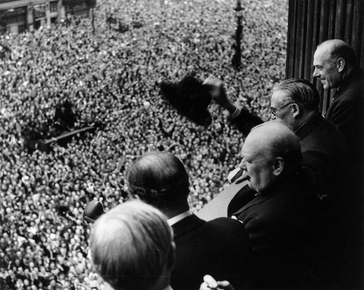 British Prime Minister Winston Churchill waves his hat to enthusiastic crowd at Whitehall, after unconditional surrender of Germany announced. (Who else is in the picture?)