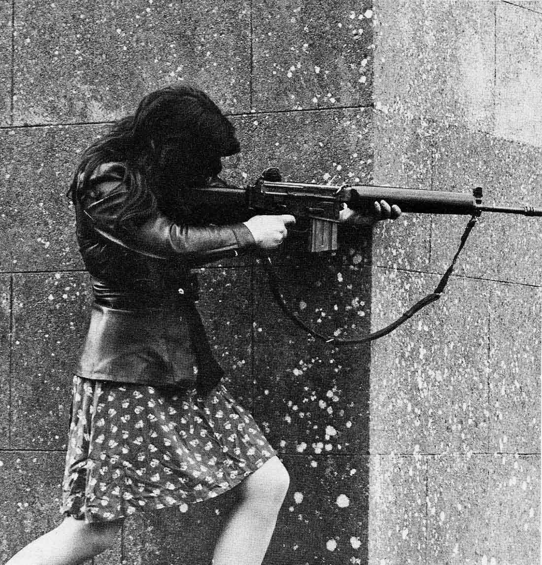 A woman IRA volunteer on active service in West Belfast with an AR18 assault rifle. 1970s