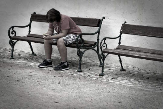photograph of sad teen on a bench