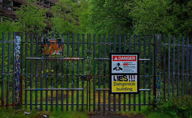"""You have been warned"" A photo of the seminary gates with asbestos warning signs, May 2013."
