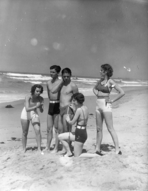 7eb1ac1544ff92 Three women wearing swimsuits and police badges measure the ...