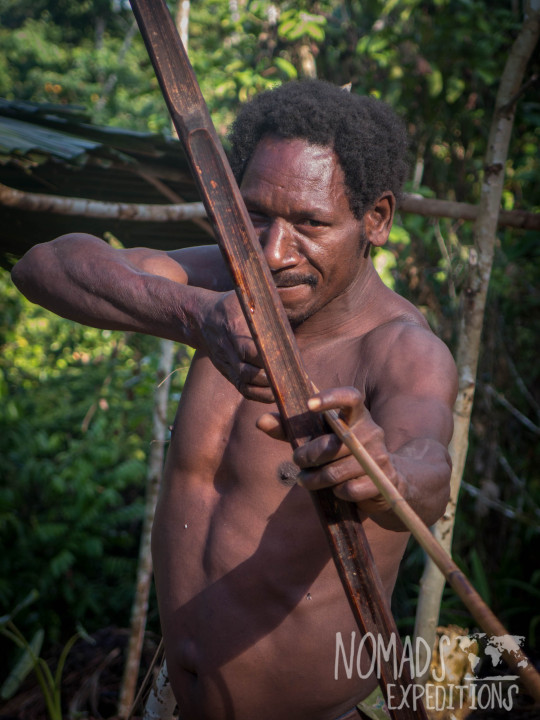 nowhere papua indonesia forest jungle wild wilderness tribal traditional culture travel adventure explore trek discover journey guide wonder dangerous survival village island tropical remote undiscovered tribesman man spear bow arrow weapon