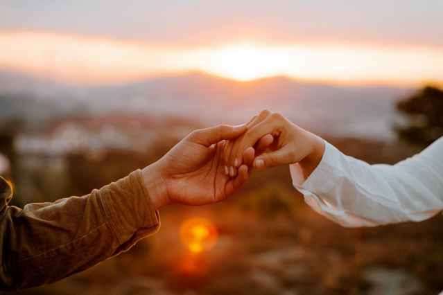 unrecognizable couple holding hands at sunset