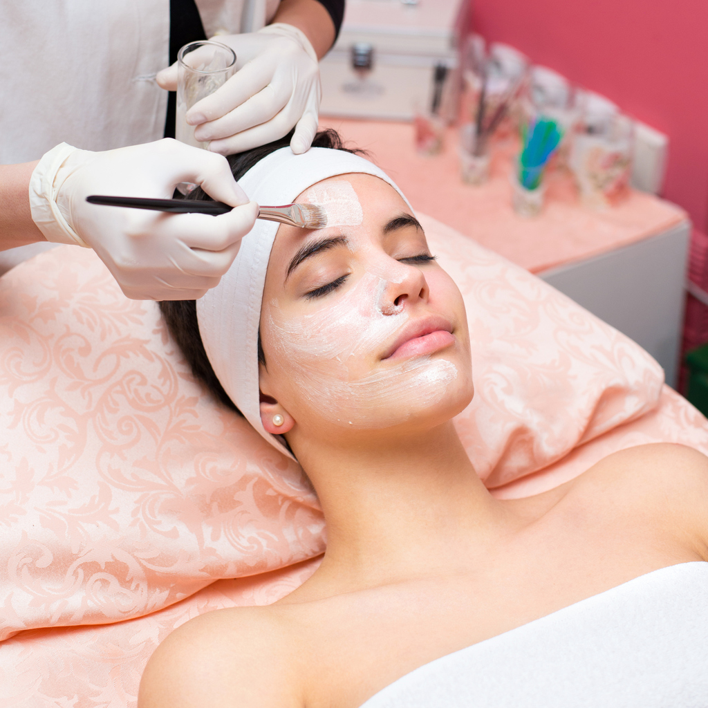 Woman getting facial mask in beauty spa