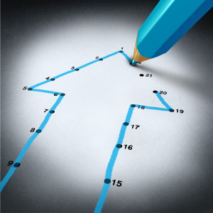 Success strategy and step by step business planning as a blue pencil drawing connection lines to connect the dots on a puzzle shaped as an arrow going up as a financial metaphor for a successful planned personal project.