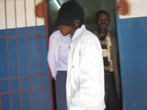 Philip Mubiana enters courtroom with his face covered. (Photo courtesy of Lukasa Times)