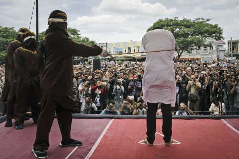 Public caning of a gay couple -- a sharia court's punishment for their homosexual activity -- was carried out May 23 outside a mosque in Banda Aceh, Aceh province, Indonesia. (Photo courtesy of The Washington Post)