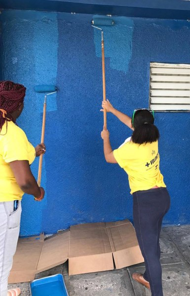 LGBT community members at Montego Bay Pride 2017 use paint rollers to spruce up the Freeport Police Station. (Photo courtesy of Maurice Tomlinson)