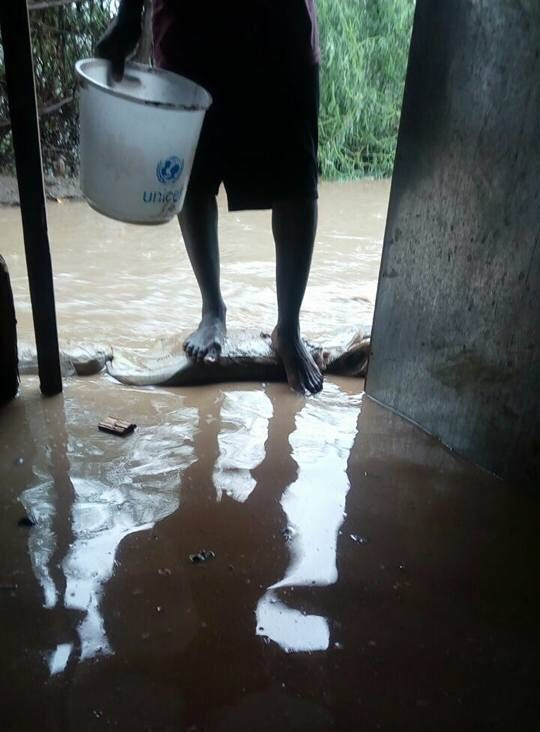 LGBTI refugee in Kakuma Camp prepares to enter his flooded shelter. (Photo courtesy of Moses Mbazira)