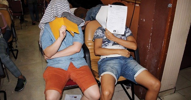 Men hide their faces at a press conference in 2017 in Indonesia after being caught in a police raid on a gay sauna in Jakarta. (Photo courtesy of Southeast Asia Globe)