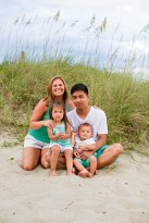 Family of 4 at the beach posing