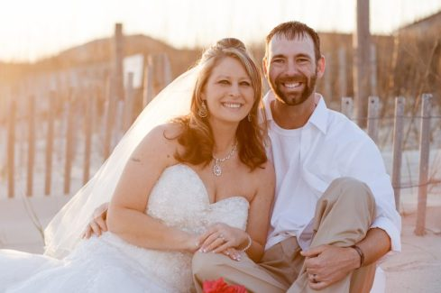 Post wedding pics in front of wooden fence in front of dunes