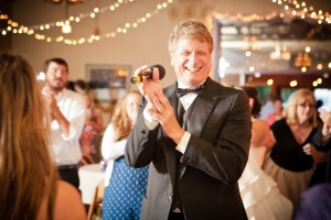 DJ Larry Hornyak in a black tuxedo clapping at a wedding.