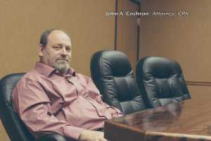 Interview John A Cochran, Esq. Photograph of John sitting at a desk in a pink dress shirt.